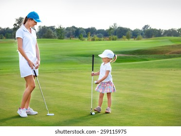 Mother and her little daughter practicing to hit the ball at the course