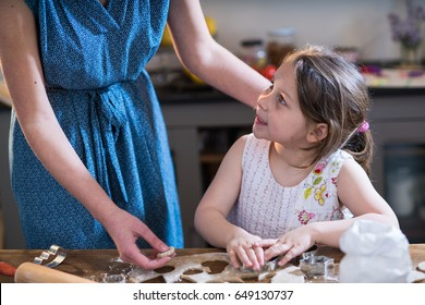 A mother and her little daughter preparing pastry in the kitchen. Little girl using metallic form to cut the dough