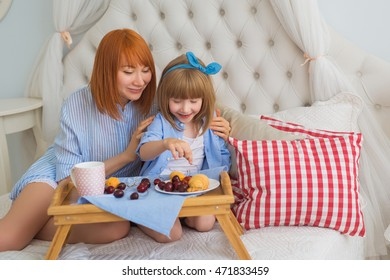 Mother and her little daughter start to eat on a bed