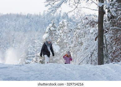 Mother and her little daughter walking through a snowy forrest