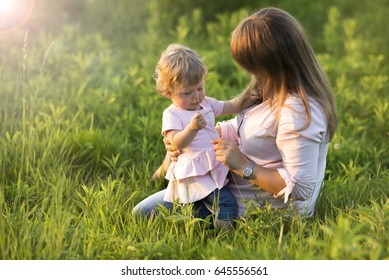 A mother with her little daughter watching flowers on a meadow