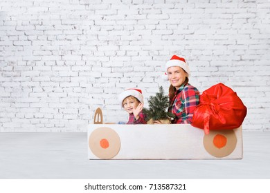 mother and her little son in Christmas hats driving a car made of cardboard box with a bag of Christmas gifts. Little boy having fun at home. Christmas concept.  New Year's holidays.