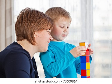 Mother and her little son playing colorful blocks at home