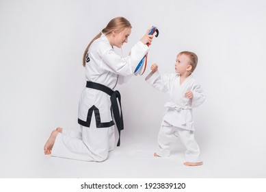 Mother her little son practicing martial arts over white background