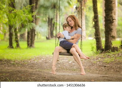 A mother and her little son ride on a swing. Wooden swings on long chains hang among palm trees and trees. Family on vacation