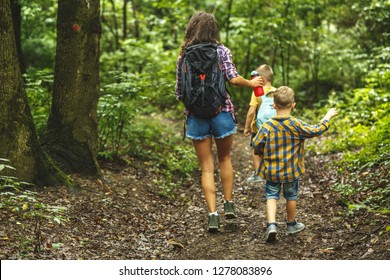 Mother and her little sons hiking trough forest.Spring concept.