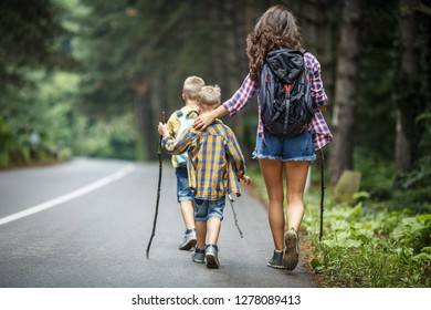 Mother and her little sons hiking by the rural country road.Outdoor spring leisure concept.