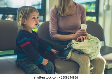 A mother and her little toddler are sitting in a waiting room