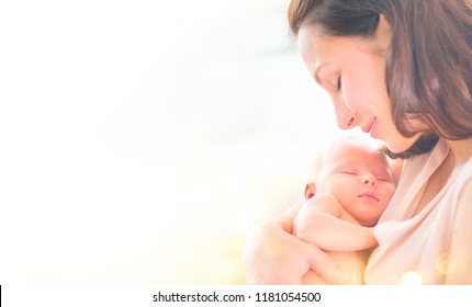 Mother and her Newborn Baby together. Love. Happy Mother and Baby kissing and hugging. High key soft image of Beautiful Family. Maternity concept. Parenthood. Motherhood, adoption