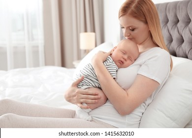 Mother with her sleeping baby in bedroom