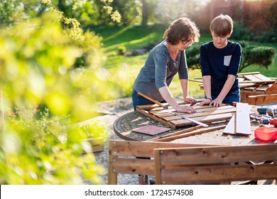 A mother and her son build wooden planters to grow organic vegetables on the terrace