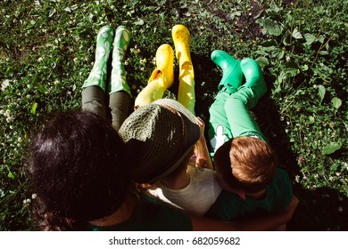 Mother, her son and daughter sitting on the grass in green and yellow gumboots