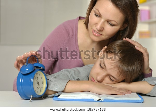 Mother with her son doing homework at home