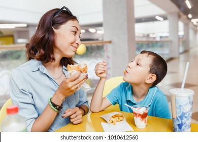Mother And her son eating a fast food hamburher Together At The Mall