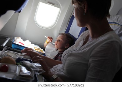 Mother with her son have lunch on the flight