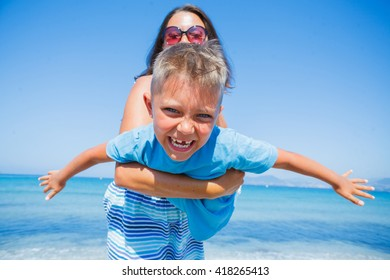 Mother with her son having fun on beautiful sunny beach
