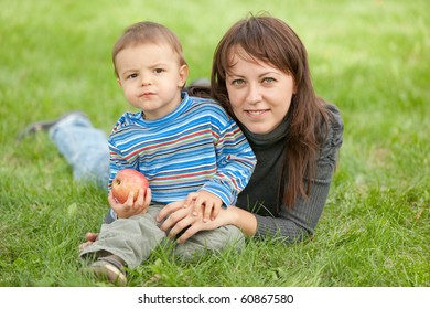 A mother and her son holding an apple are resting on the green meadow