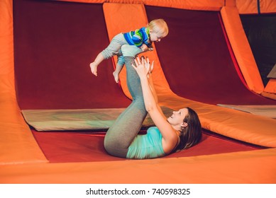 Mother And her son jumping on a trampoline in fitness park and doing exersice indoors.