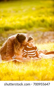 Mother with her son lying on the grass. Family spending quality time together