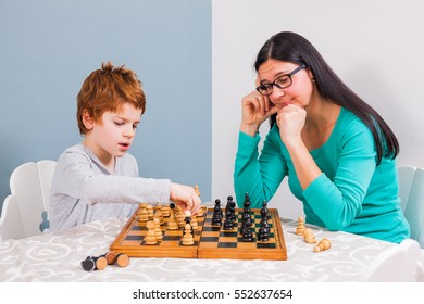 Mother and her son are playing chess at home.