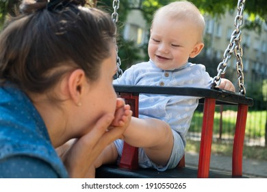 Mother and her son playing on a swing. Mother swinging her baby. Boy on a swing.