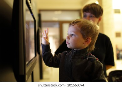 Mother and her son playing with touch screen in a museum
