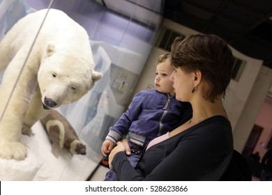Mother with her son and polar bear in zoological museum