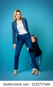 Mother and her son are posing in the studio and wearing casual clothes. Family, fashion.