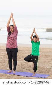 Mother with her son practicing yoga on exercise mat at beach