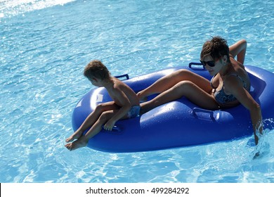 Mother with her son riding at water slide in aquapark