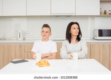 Mother and her son sitting at table and looking at different sides after quarrel. Copcept of family conflict