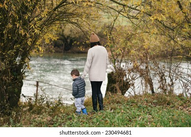 Mother and her son standing by the river in autumn