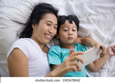 mother and her son Taking pictures or selfie or video call or relatives in a bed. Concept of new generation, family, parenthood, authenticity, connection