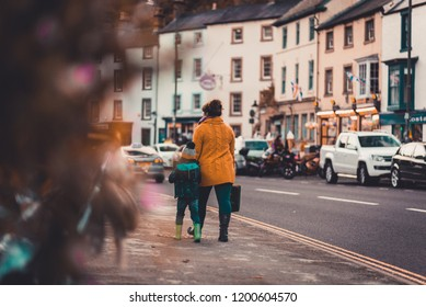 A mother and her son walk down a busy street toward the Matlock Bath Illuminations in October, 2018