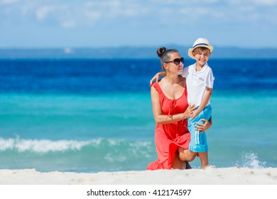 Mother with her son walking on beautiful sunny beach