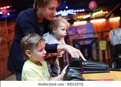 Mother with her sons playing at amusement park