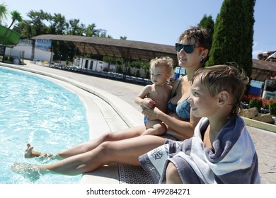Mother with her sons sitting on edge of pool in aquapark