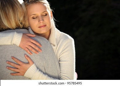 A mother and her teenage daughter hugging.