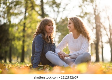 Mother and her teenage daughter sitting on grass and talking with nature in background