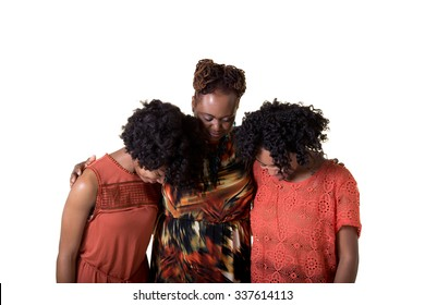 A mother and her teenage daughters bowing to pray