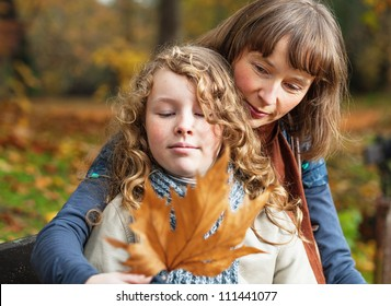 Mother and her teenager daughter sitting on a bench in an autumn park and looking at fallen leaf