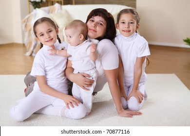 mother with her three daughters at home on the carpet in the living  room