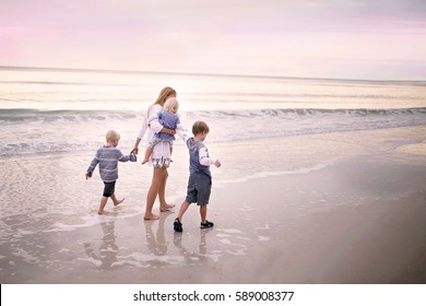 A mother and her three young children, including a baby, are holding hands and walking along the ocean shore on a white sand beach in Marco Island, Florida at sunset.