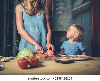 A mother and her toddler are making sandwiches at home
