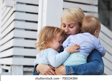 Mother and her two baby laughing and hugging