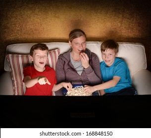 Mother and her two boys watching a comedy Movie at home