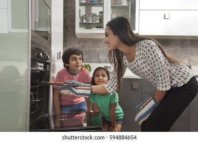 Mother with her two children baking in oven