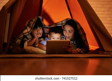 Mother and her two children lying under blanket and watching movies