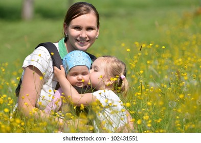mother with her two daughters on meadow