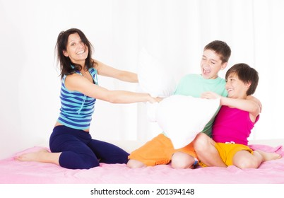 mother and her two sons having a pillow fight in bedroom